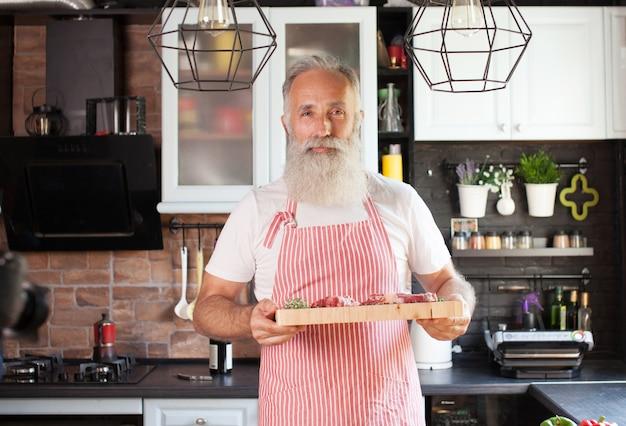 Plan moyen du chef mature souriant avec planche à découper à la main. viande gisant sur le plateau. homme isolé dans une cuisine moderne bien agencée.