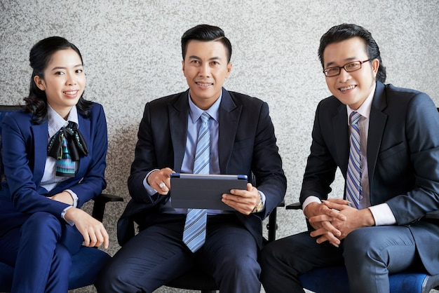 Plan moyen d'une équipe de professionnels assis au bureau avec une tablette pc