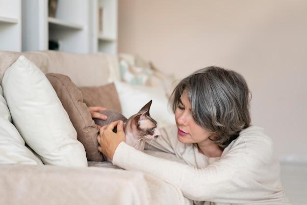 Plan moyen femme caresser le chat
