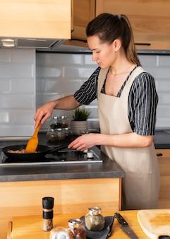 Plan moyen femme cuisson sur cuisinière