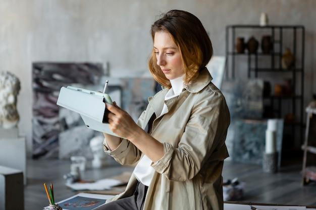 Plan moyen femme dessin sur tablette