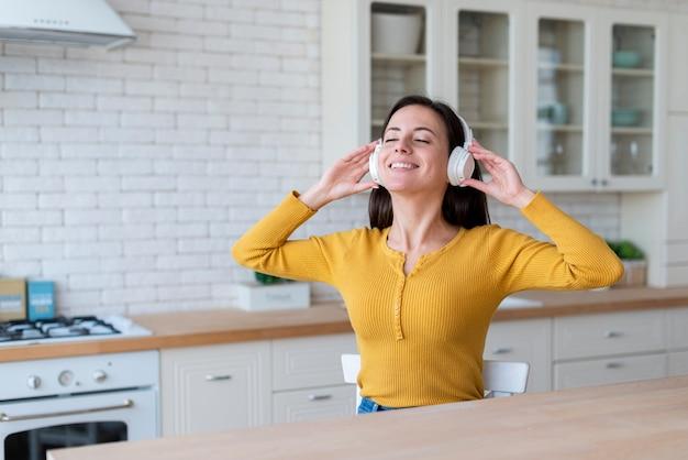 Plan moyen d'une femme écoutant de la musique