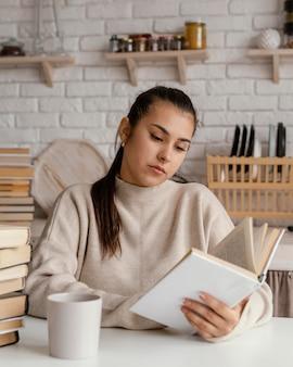 Plan moyen femme lisant dans la cuisine