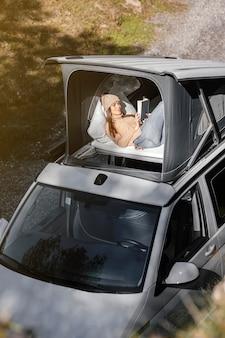 Plan moyen femme lisant pendant un voyage sur la route