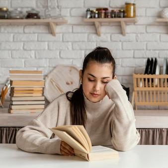 Plan moyen femme lisant à table