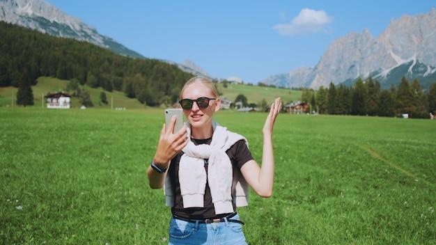 Plan moyen d'une femme passant un appel vidéo depuis un magnifique parc naturel en face des montagnes. elle partage les impressions de son voyage.