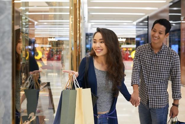 Plan moyen d'une femme pointant au magasinage qui montre l'objet désiré à son mari