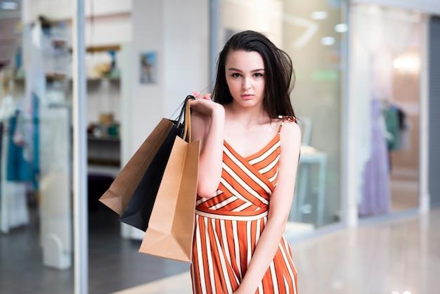 Plan moyen femme posant dans le centre commercial