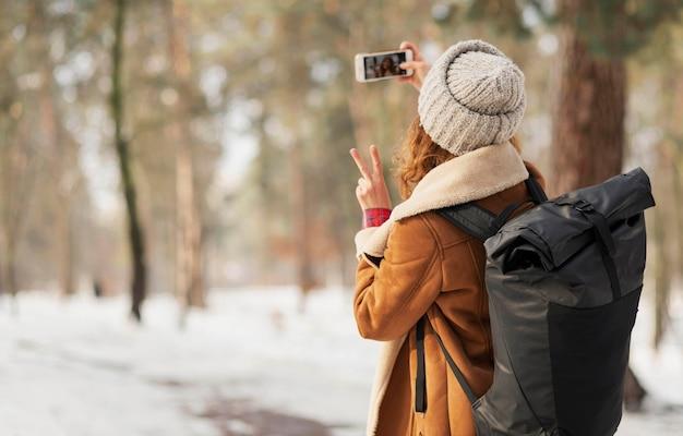 Plan moyen femme prenant selfie à l'extérieur