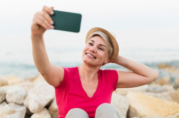 Plan moyen femme prenant selfie