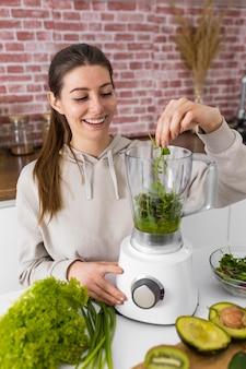 Plan moyen femme préparant un smoothie