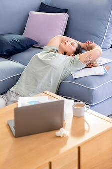 Plan moyen femme qui s'étend sur le canapé