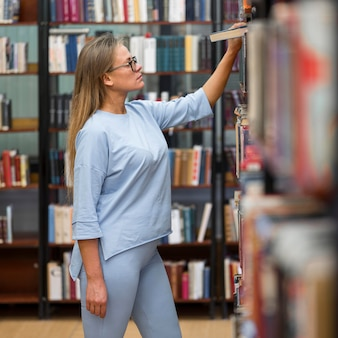 Plan moyen femme à la recherche de livres