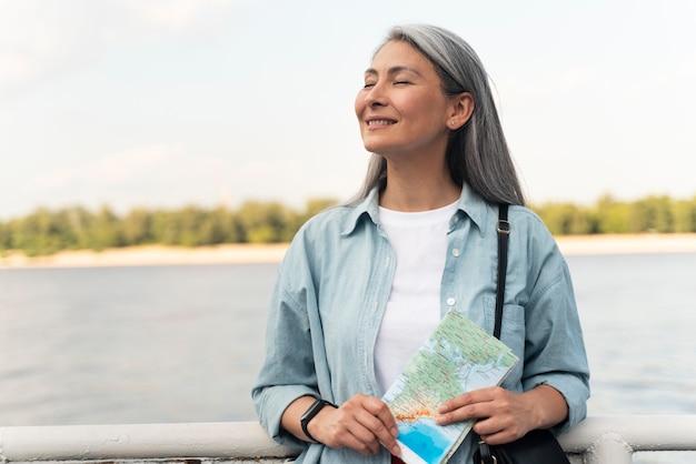 Plan moyen femme souriante tenant la carte