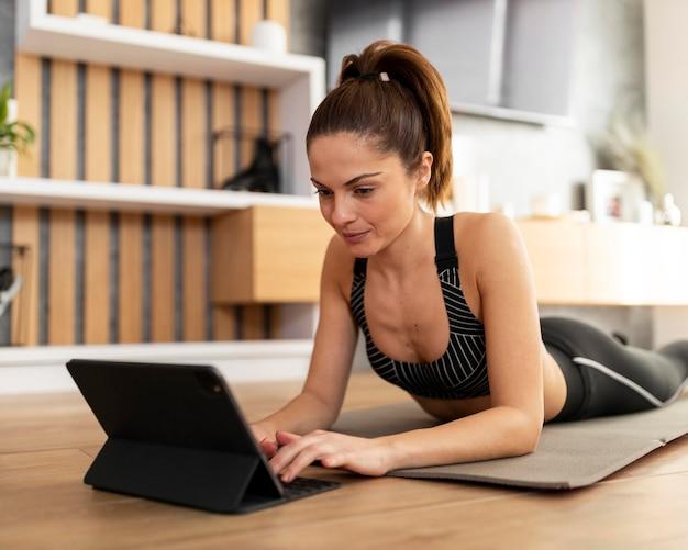 Plan moyen femme sur tapis avec tablette