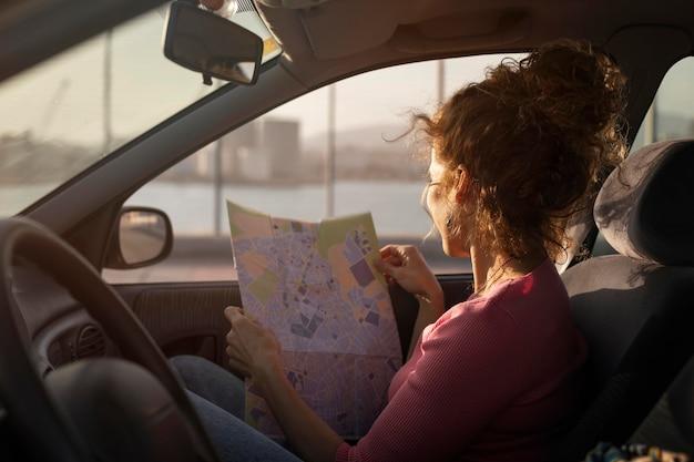 Plan moyen femme tenant une carte en voiture