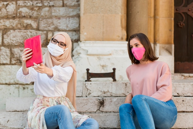 Plan moyen femmes prenant selfie à l'extérieur