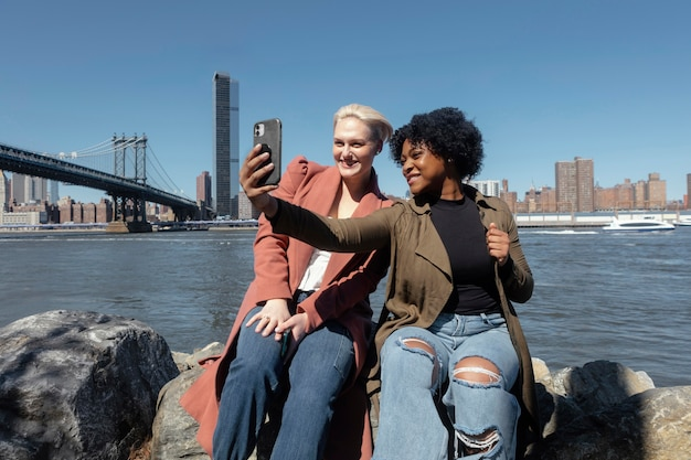 Plan moyen femmes prenant selfie à new york