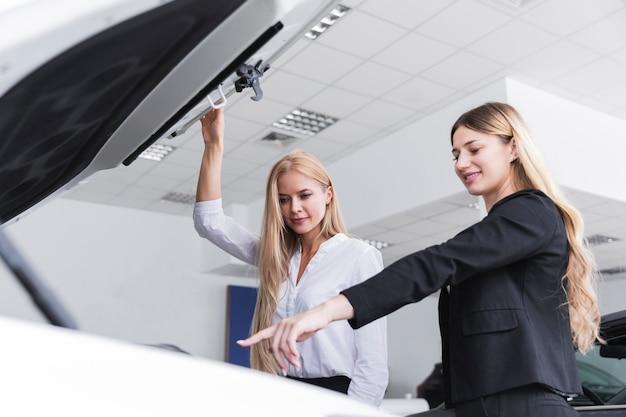 Plan moyen de femmes vérifiant le moteur d'une voiture