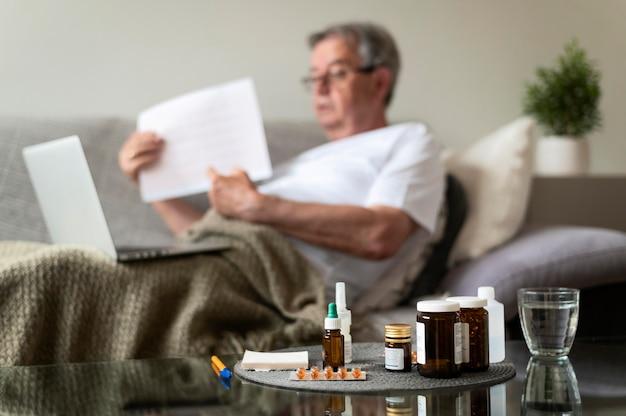 Plan moyen flou homme malade sur canapé
