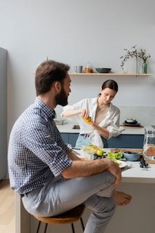 Plan moyen des gens discutant dans la cuisine
