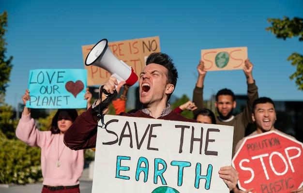 Plan moyen des gens qui protestaient avec des pancartes