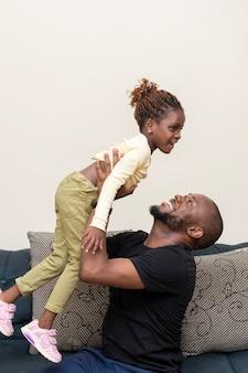 Plan moyen heureux père tenant fille