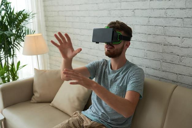 Plan moyen d'un homme jouant à un jeu de réalité virtuelle sur le canapé à la maison