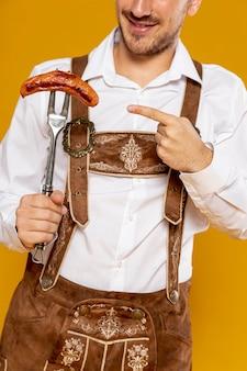 Plan moyen d'un homme montrant une saucisse