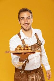 Plan moyen d'un homme avec un plateau de saucisses