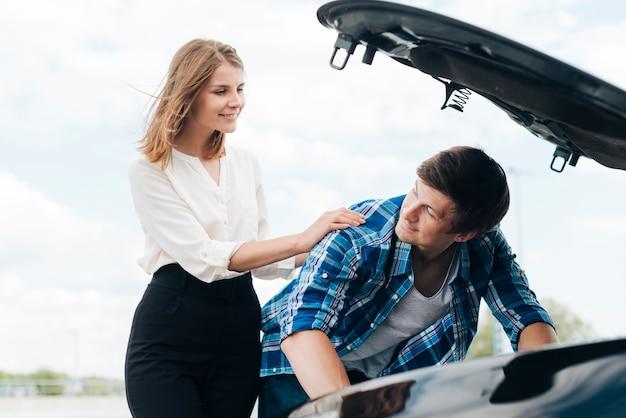 Plan moyen d'un homme travaillant sur une voiture