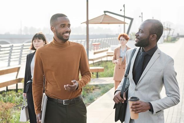 Plan moyen horizontal de deux hommes afro-américains marchant ensemble le long de la rue en train de parler de quelque chose après avoir terminé la journée de travail au bureau