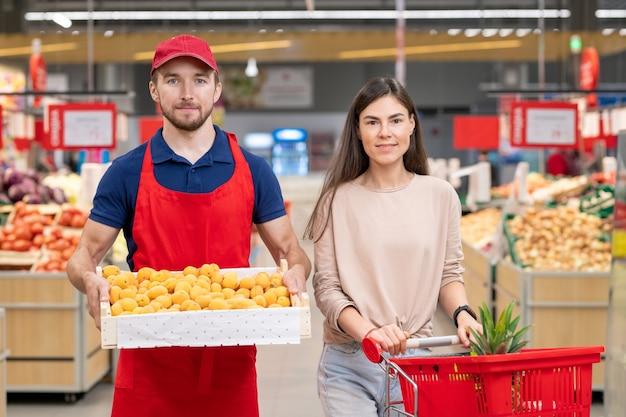Plan moyen horizontal d'un travailleur masculin tenant une boîte d'abricots debout avec une jeune cliente dans l'allée du supermarché