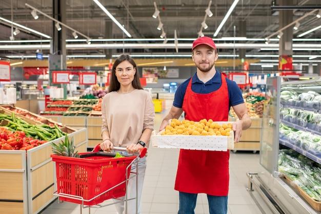 Plan moyen horizontal d'un travailleur masculin tenant une boîte de fruits debout avec une jeune cliente dans un supermarché