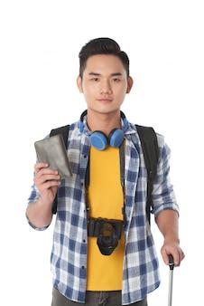 Plan moyen d'un jeune touriste avec des bagages, titulaire du passeport et face à la caméra