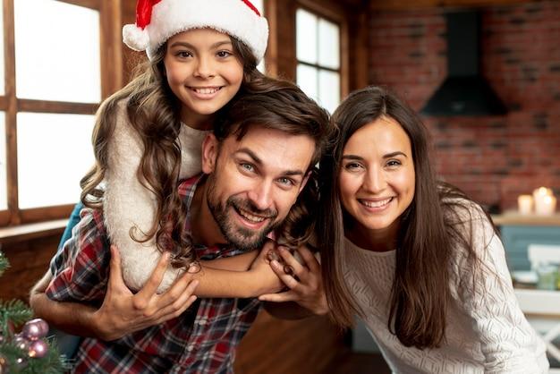 Plan moyen parents heureux et fille posant à l'intérieur