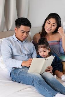 Plan moyen parents lisant à l'enfant