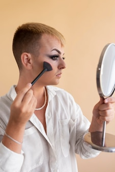 Plan moyen transgenre se maquillant