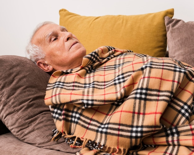 Plan moyen vieil homme portant sur le canapé
