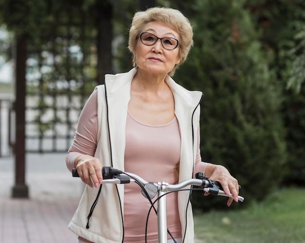 Plan moyen vieille femme avec vélo