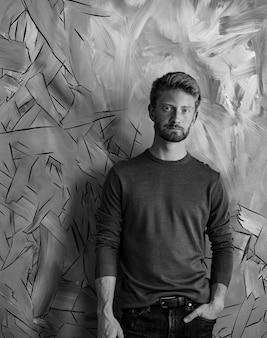 Plan en niveaux de gris d'un beau mec avec sa main dans une poche près du mur