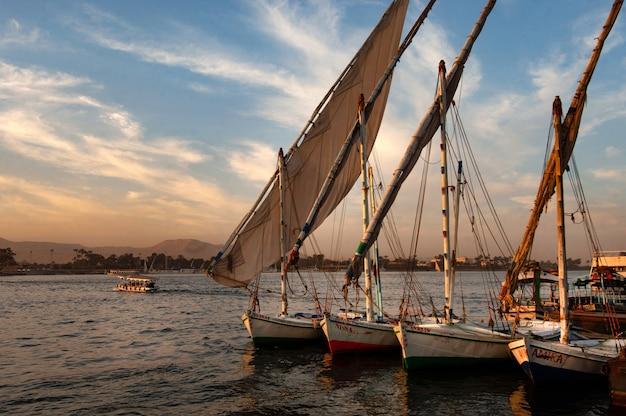 Plan de nombreux bateaux amarrés près de la jetée en lignes droites au coucher du soleil