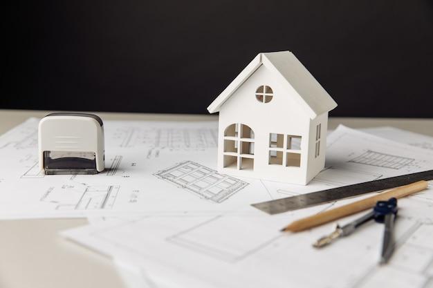 Plan avec des outils de dessin de maison blanche et des lunettes sur une table