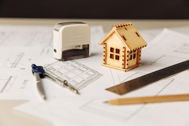 Plan avec des outils de dessin de maison en bois et des lunettes sur une table