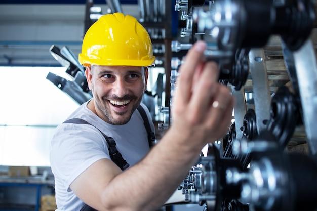 Plan d'un ouvrier d'usine caucasien portant un casque jaune vérifiant la qualité des produits dans l'industrie.