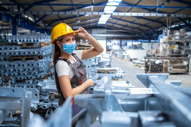 Plan d'une ouvrière d'usine en uniforme et casque portant un masque facial dans une usine de production industrielle
