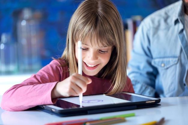 Plan d'une petite fille assez heureuse qui dessine avec une tablette numérique à la maison.