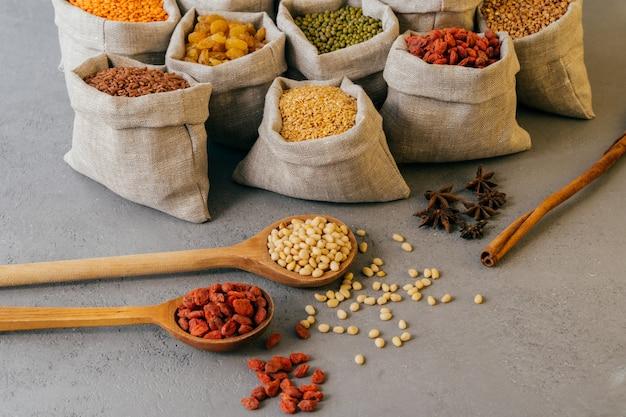 Plan de petits sacs avec des céréales colorées, des légumineuses nutritives, de l'anis étoilé à proximité, deux cuillères en bois avec des baies de goji rouges. produits crus