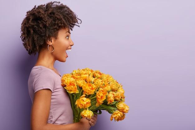 Plan de profil d'une femme afro-américaine surprise énergique regarde au loin, ne peut pas en croire ses yeux, porte un t-shirt décontracté