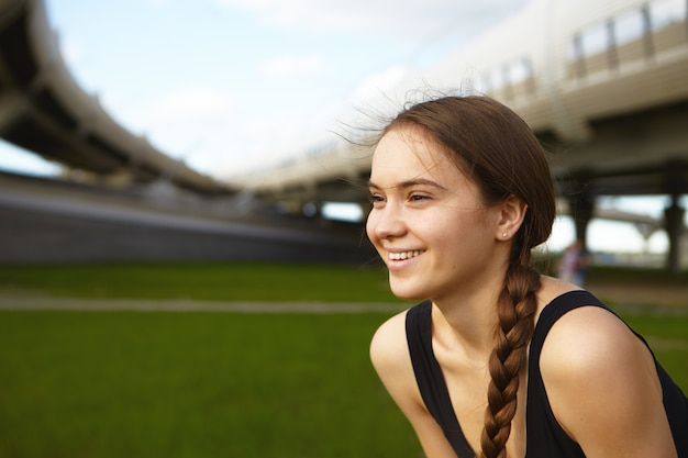 Plan de profil d'une jeune athlète féminine de race blanche attrayante aux cheveux noirs rassemblés en tresse, souriant largement, profitant du beau temps d'été pendant les exercices en plein air au stade. sports et fitness